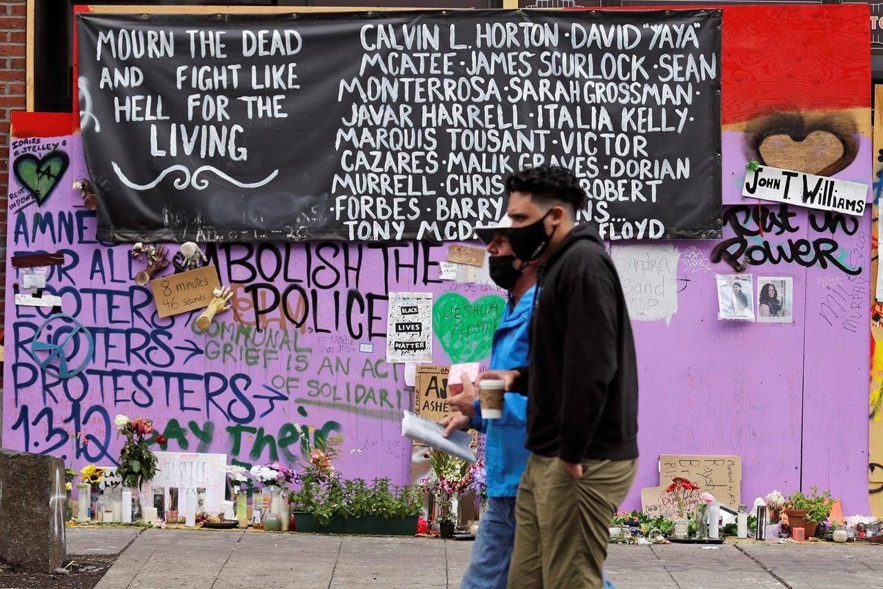Two people walk past a memorial Sunday, June 28, 2020, in Seattle, for people of color believed to have died in police custody, where several streets are blocked off in what has been named the Capitol Hill Occupied Protest zone. Seattle Mayor Jenny Durkan met with demonstrators Friday after some lay in the street or sat on barricades to thwart the city's effort to dismantle the protest zone that has drawn scorn from President Donald Trump and a lawsuit from nearby businesses. (AP Photo/Elaine Thompson)