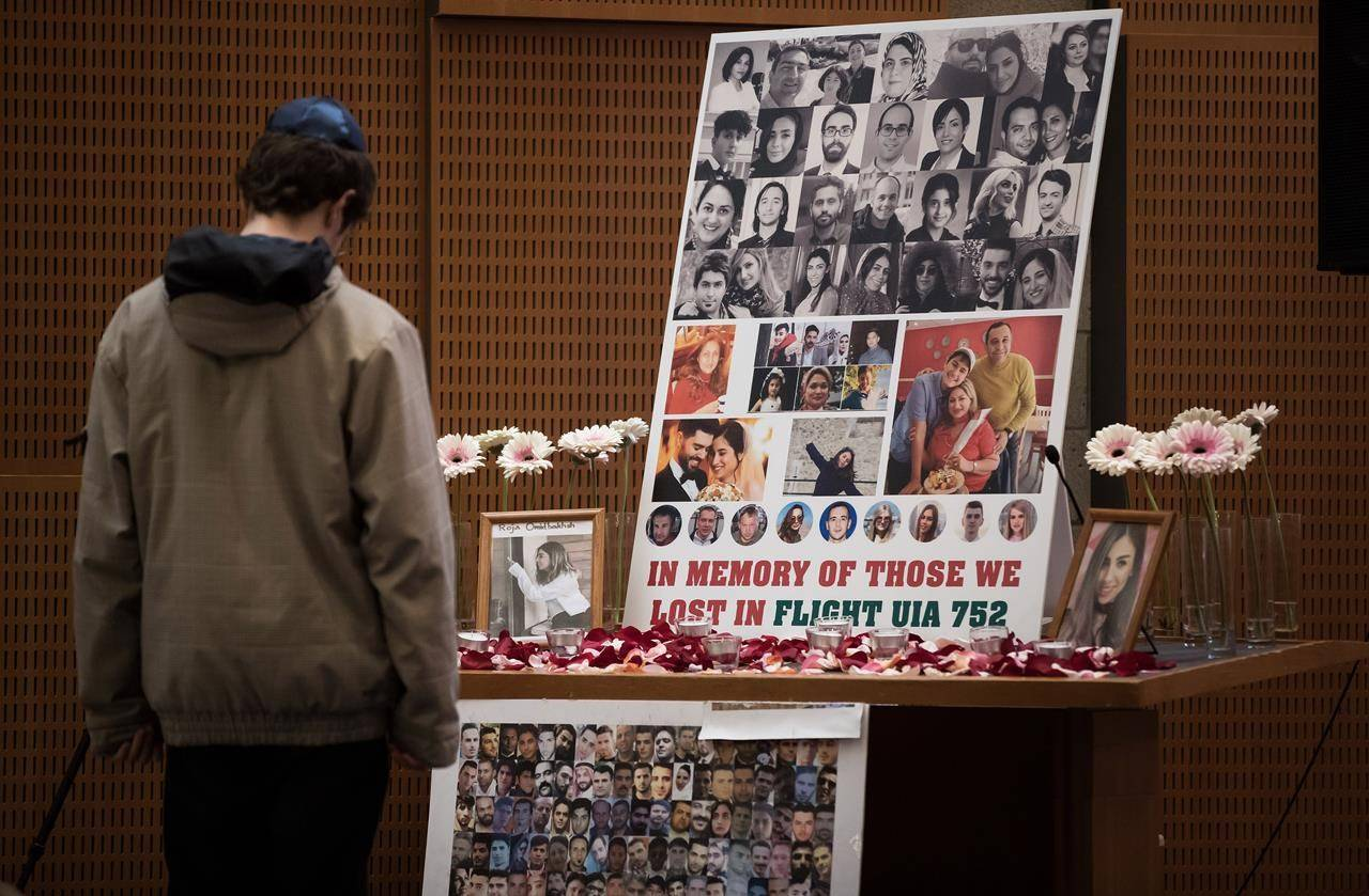 A man pauses to look at photographs of some of the people who died in the downing of Ukrainian Airlines Flight 752 in Iran, during a vigil for the victims of the flight at the Har El synagogue in West Vancouver on January 19, 2020. THE CANADIAN PRESS/Darryl Dyck