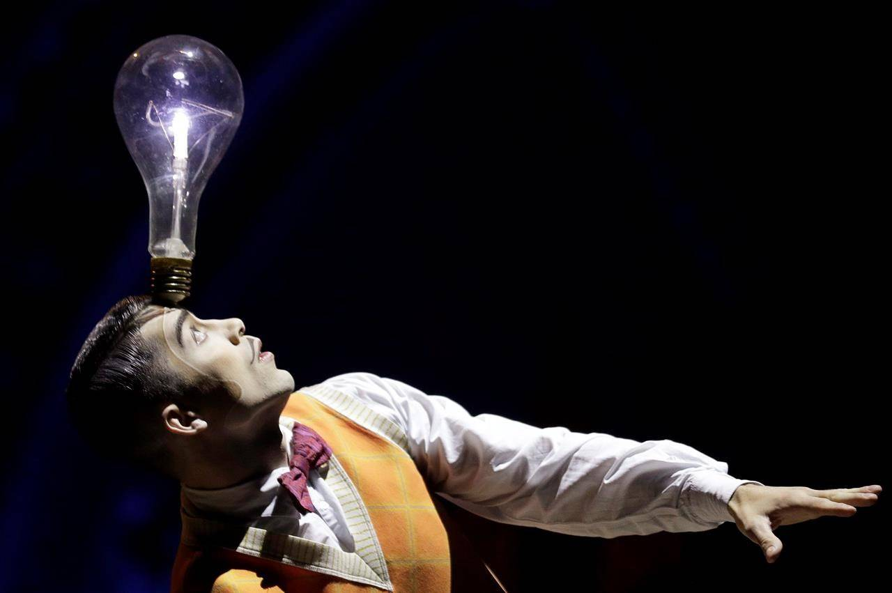 """FILE – A performer balances a lightbulb on his head during a preview of the Cirque Du Soleil production of """"Kurios - Cabinet of Curiosities"""" in Sydney, Tuesday, Oct. 1, 2019. THE CANADIAN PRESS/AP/Rick Rycroft"""