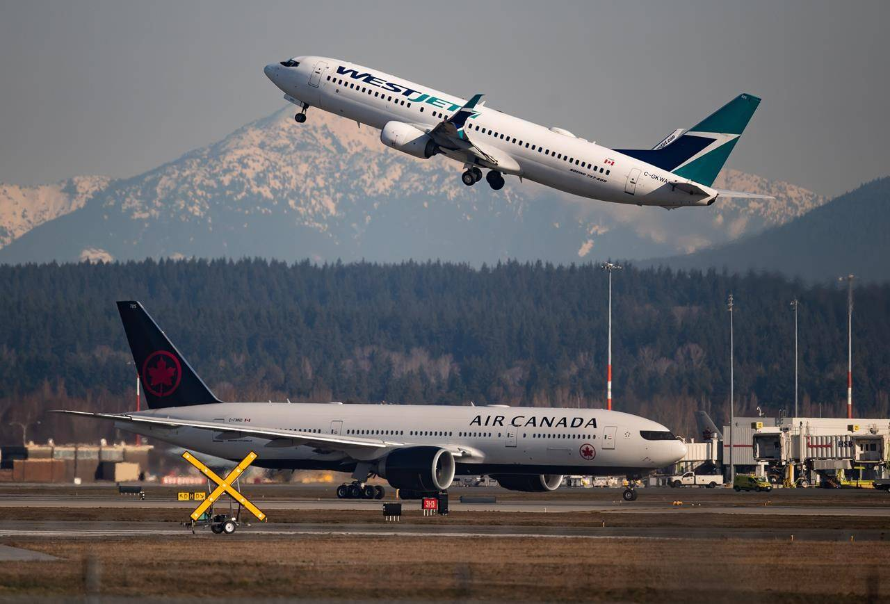 An Air Canada flight departing for Toronto, bottom, taxis to a runway as a Westjet flight bound for Palm Springs takes off at Vancouver International Airport, in Richmond, B.C., on Friday, March 20, 2020. British Columbia Health Minister Adrian Dix says he wants to see the evidence that it's safe for the country's two largest airlines to drop their in-flight distancing policies during the pandemic. THE CANADIAN PRESS/Darryl Dyck