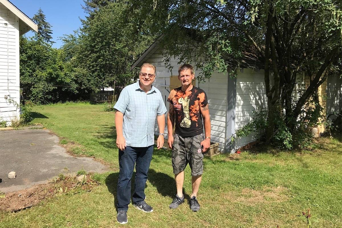Bruce Hitchen, Holy Cross Ukrainian Catholic Parish president, left, and 51-year-old Gordon Petrie, who has been living in the dirt-floor shed the pair are standing in front of in Whalley. (Photo submitted)