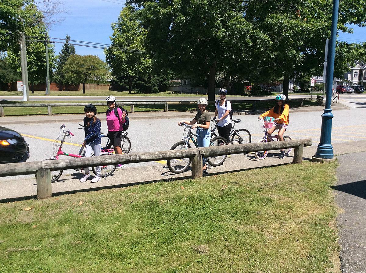 Yurim Lee (left), Stephanie Norris, Ava Demuynck, Maria Fawcett, and Shia Sumra bike around Cloverdale on a school field trip June 18. (Photo submitted)