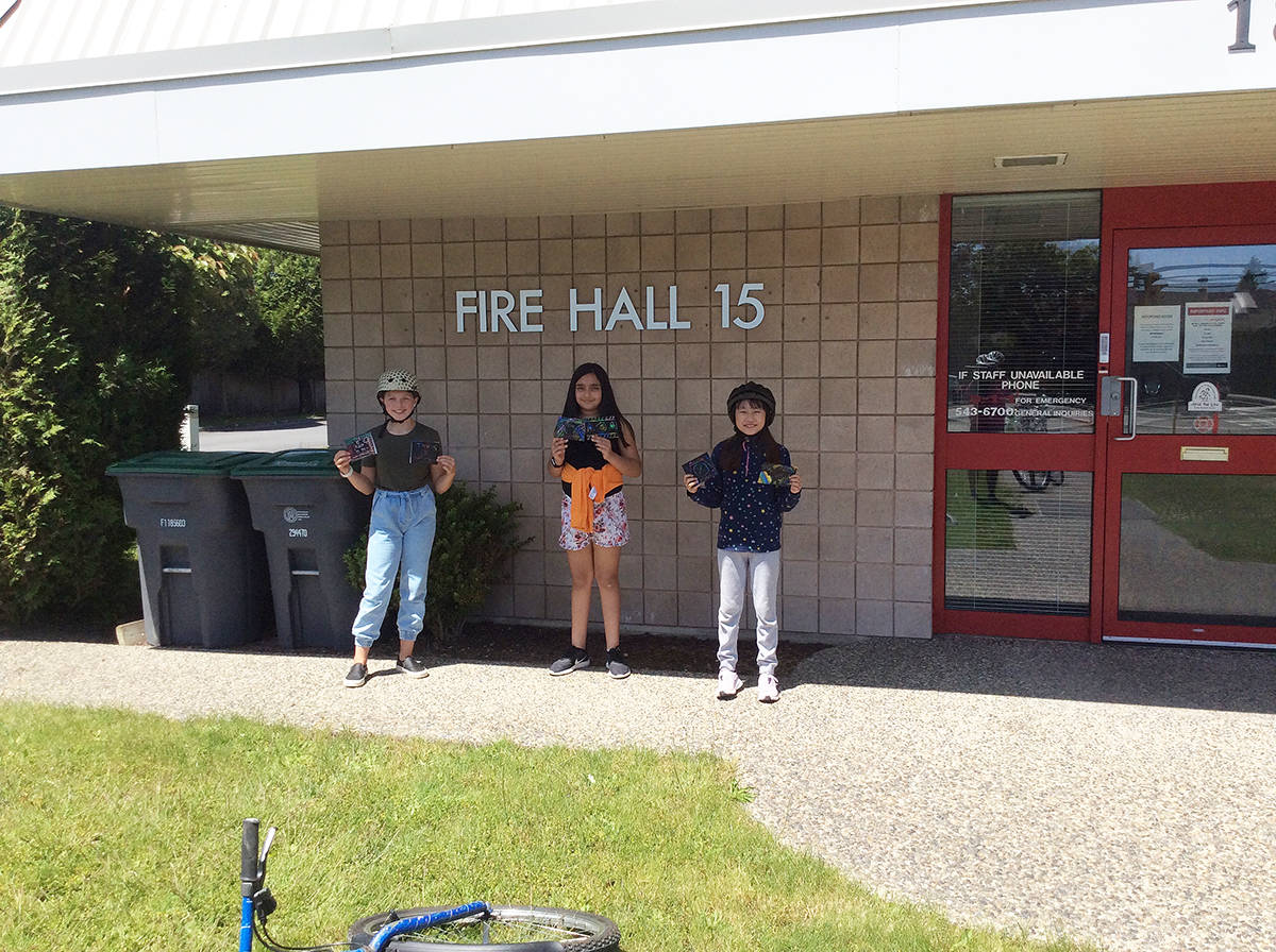 Ava Demuynck (left), Shia Sumra, and Yurim Lee hold up thank you notes they were delivering to the firefighters at Hall 15. (Photo: Stephanie Norris)
