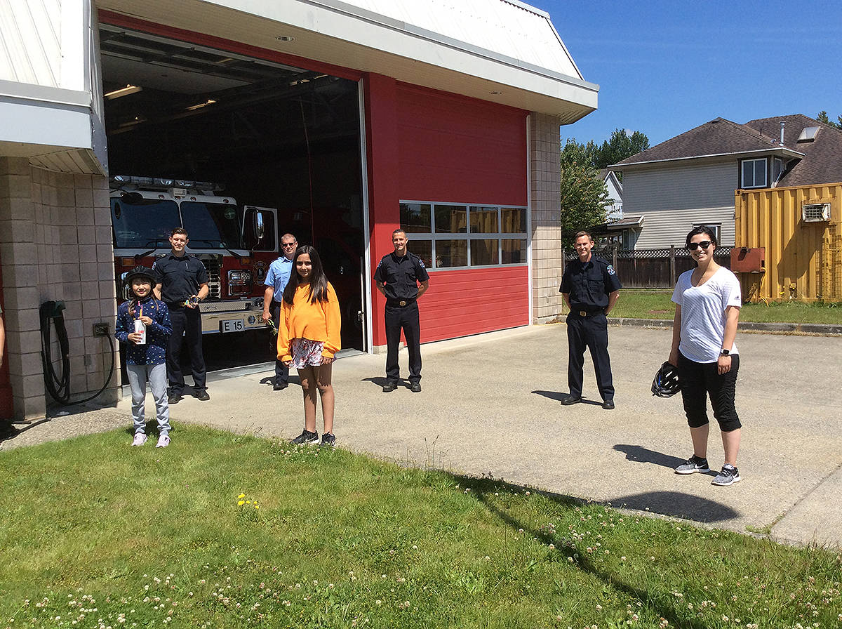 Yurim Lee (left), Shia Sumra, and student-teacher Maria Fawcett stand with firefighters from Cloverdale's Hall No. 15 in June. The students delivered thank you notes from their class to the first responders. (Photo: Stephanie Norris)