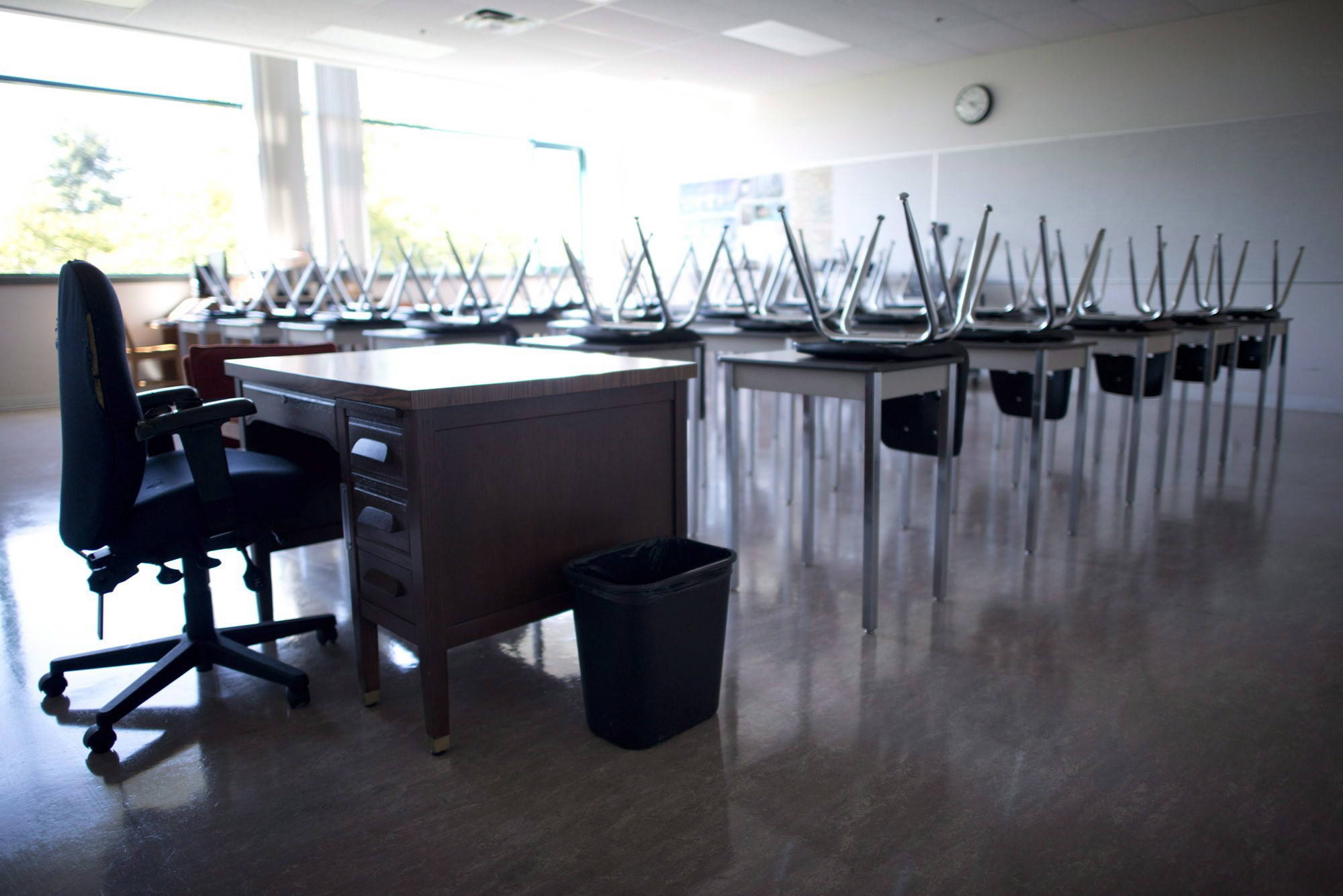 A empty teacher's desk is seen at the front of a empty classroom at McGee Secondary school in Vancouver on September 5, 2014. Many parents are figuring out daily plans on the homefront in the wake of school closures around the country.THE CANADIAN PRESS/Jonathan Hayward