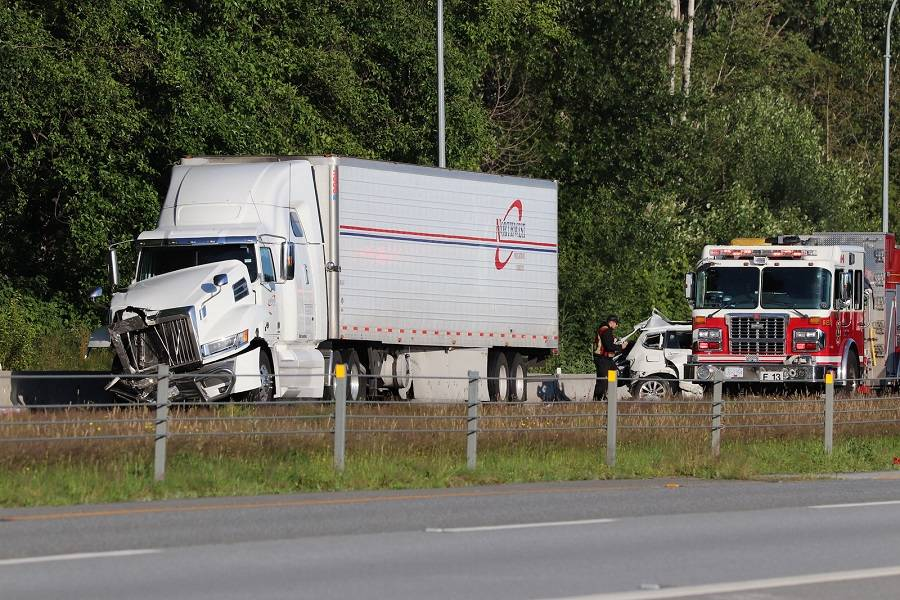 At least one person was taken to hospital Saturday (July 4) following a collision between a BMW and a semi-trailer on Highway 99 in South Surrey. (Shane MacKichan photo)
