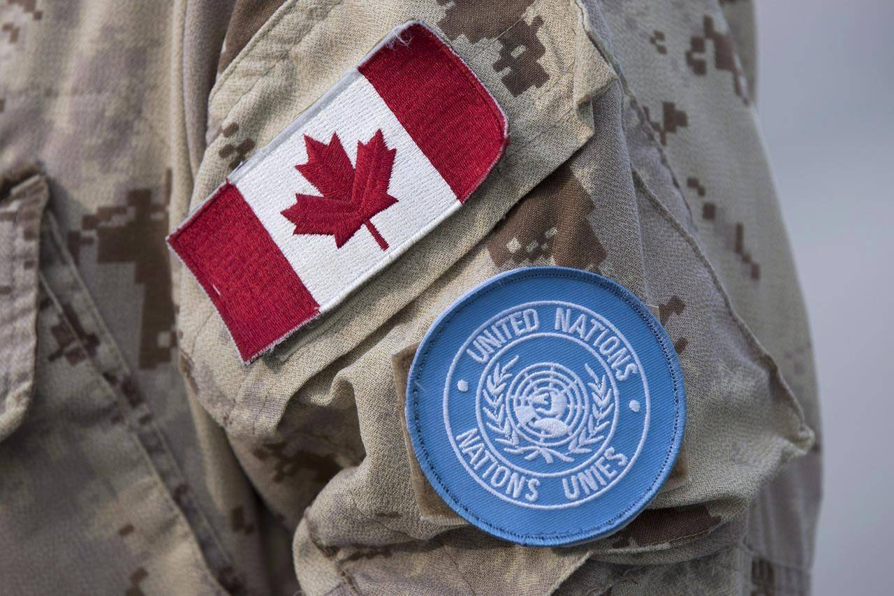 Canadian flag and the UN flag is shown on the sleeve of a Canadian soldier's uniform before boarding a plane at CFB Trenton in Trenton, Ont., on July 5, 2018. A military plane carrying Canadian troops to Latvia was forced to turn around because of concerns those on board might have been exposed to COVID-19. Defence Department spokeswoman Jessica Lamirande says the Polaris aircraft carrying about 70 military members and aircrew took off from Canadian Forces Base Trenton on July 2 those on board had spent two weeks in quarantine. THE CANADIAN PRESS/Lars Hagberg