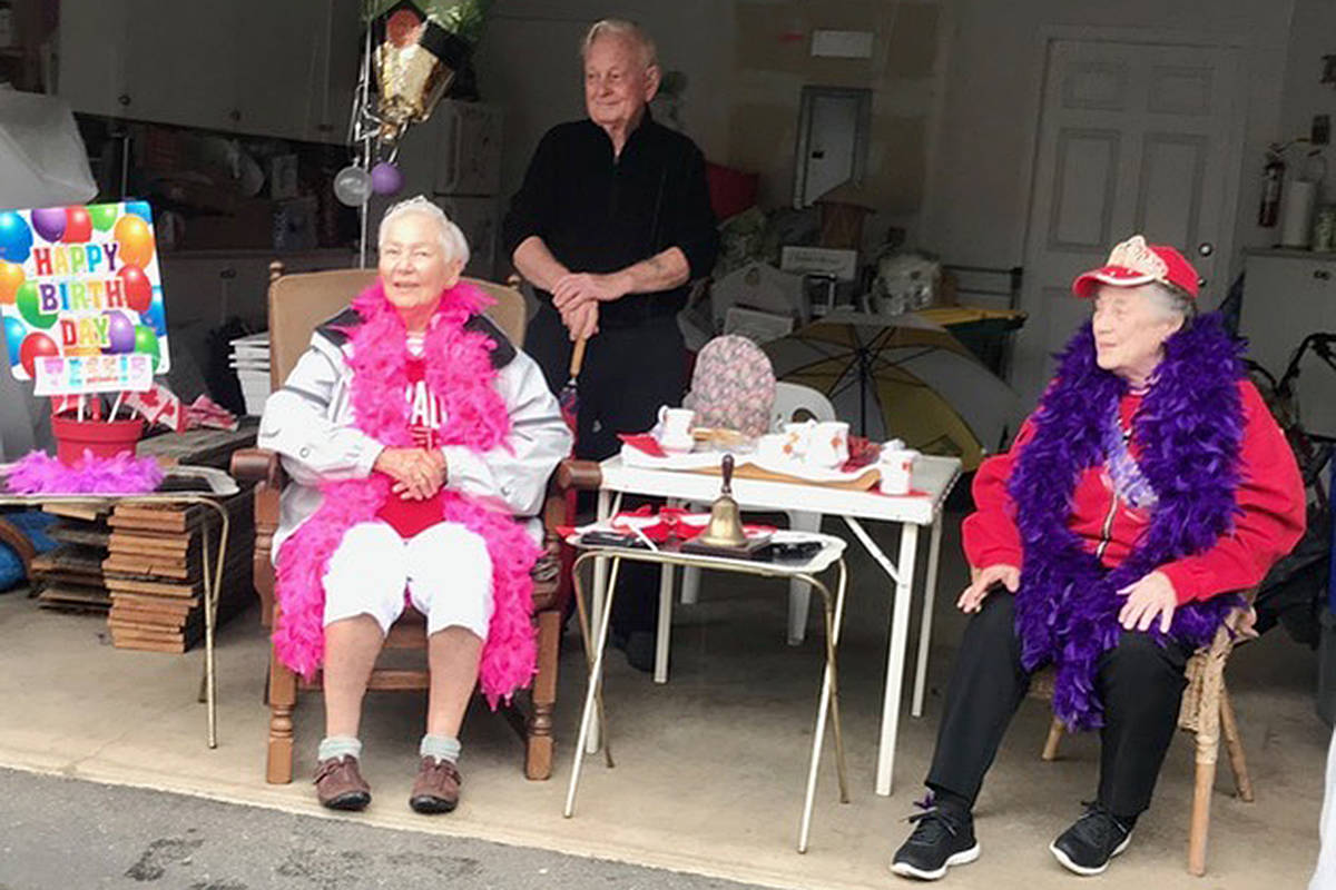 Birthday gals Tessie Copeman, 86, and Barrie Geosits, 85, along with Ed Hendricks, stayed dry while watching the Chartwell Green Canada Day parade. (Bev Genge/Special to the Langley Advance Times)
