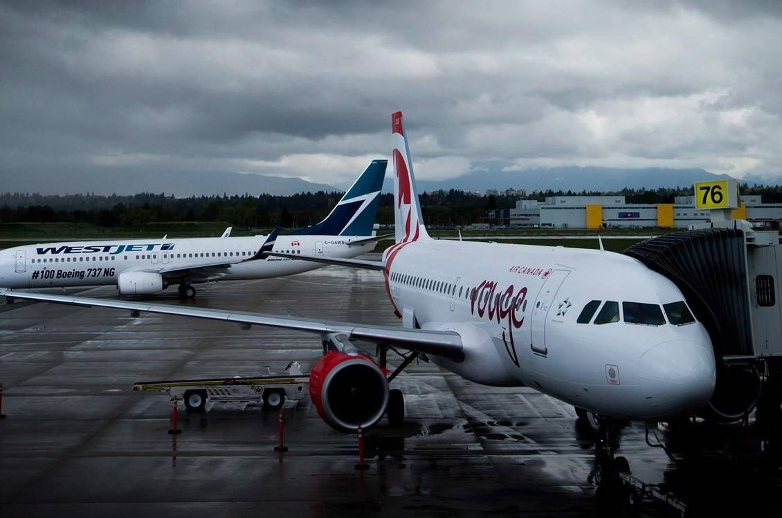 A Westjet Boeing 737-800, left, taxis past an Air Canada Rouge Airbus A319 at Vancouver International Airport in Richmond, B.C., on Monday, April 28, 2014. A new poll suggests turbulence ahead when it comes to the airlines winning public support for their current COVID-19 plans. THE CANADIAN PRESS/Darryl Dyck