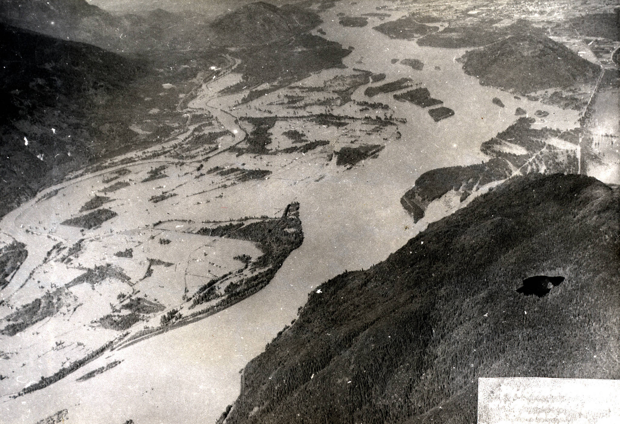 An aerial view, without horizon, of the Fraser River and part of Sumas Mountain, during the 1948 Fraser River flood. Nicomen Island is seen inundated with flood water at top centre in image. Chilliwack Mountain is visible at top right (1948). (Photograph courtesy of the Chilliwack Museum and Archives P669).