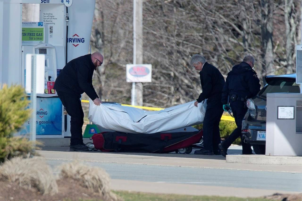 Workers with the medical examiner's office remove a body from a gas bar in Enfield, N.S. on Sunday, April 19, 2020. A coalition of groups devoted to reducing or eradicating gender based violence across Canada is urging Ottawa and Nova Scotia to refrain from using a restorative justice approach for a promised inquiry into the mass killing that claimed the lives of 22 people in the Maritime province. THE CANADIAN PRESS/Andrew Vaughan