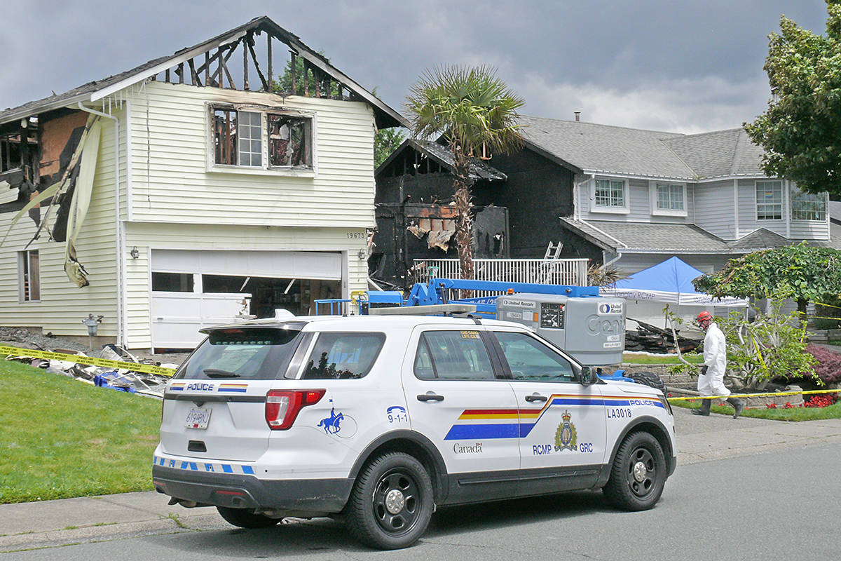 Police remained on the scene June 16, 2020, of the fatal house fire that destroyed the light yellow house on the left in the 19600 block of Wakefield Drive in Langley and causing substantial damage to the grey house on the right where the Wenzoski family lived (Dan Ferguson/Langley Advance Times)