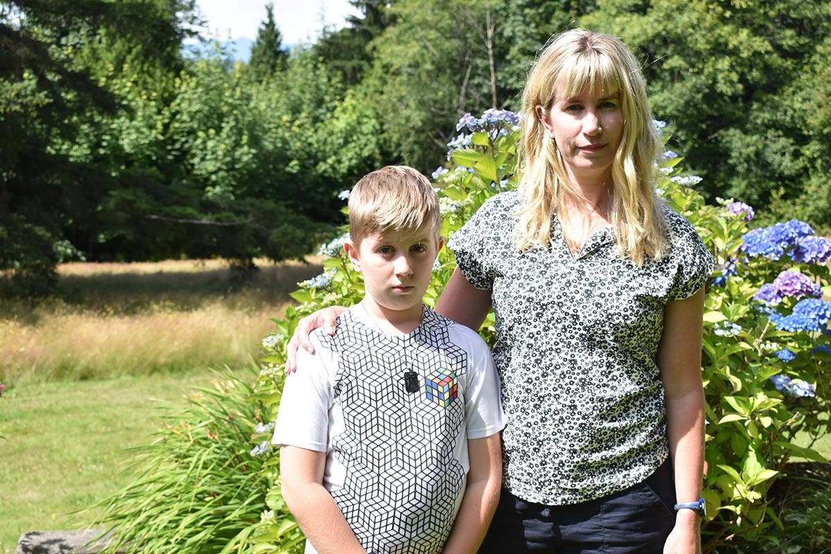Calla Oxley and her son Wade stand on their neighbours property, which backs on to Bayview Woods Park. Oxley says her son sustained an allergic reaction after playing in the tall grass. (Aaron Hinks photo)