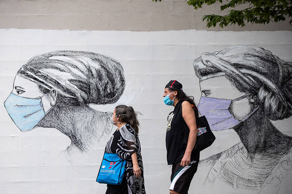 People wearing protective face masks walk past artwork of women wearing masks, on the side of a building in Vancouver, on Sunday, May 31, 2020. THE CANADIAN PRESS/Darryl Dyck