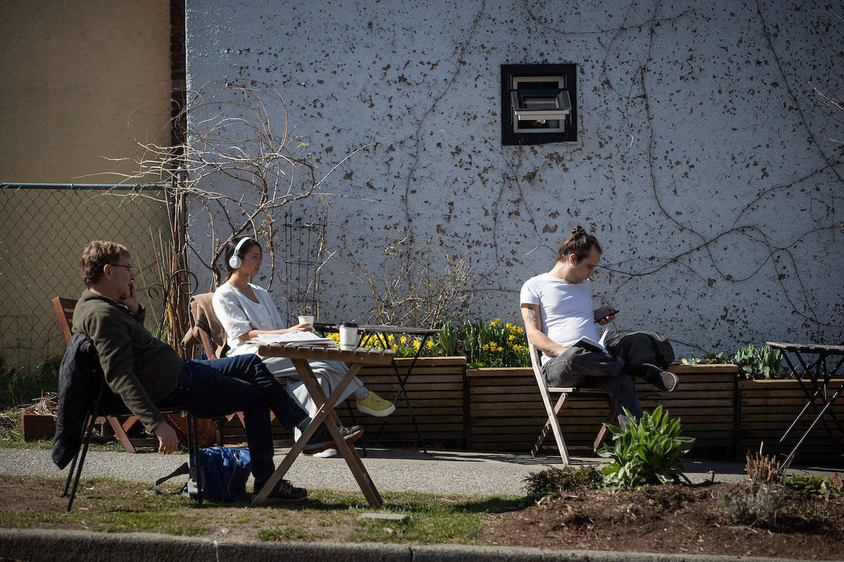 People maintain distance between one another while sitting outside a general store, amid concerns about the coronavirus in Vancouver, on Friday, March 20, 2020. THE CANADIAN PRESS/Darryl Dyck