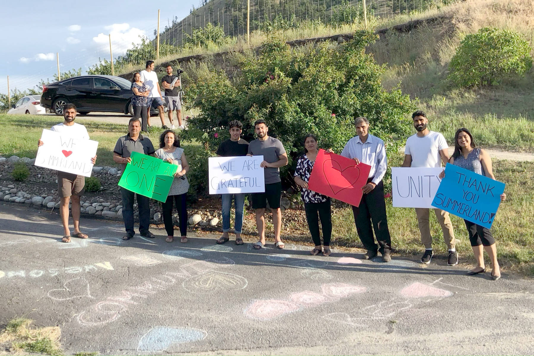Members of the Lekhi family in Summerland held signs of gratitude on July 16. The family home had been spray painted with racist graffiti earlier in the week. A parade on July 16 was held as a show of support for the Indo-Canadian family. (John Arendt - Summerland Review)