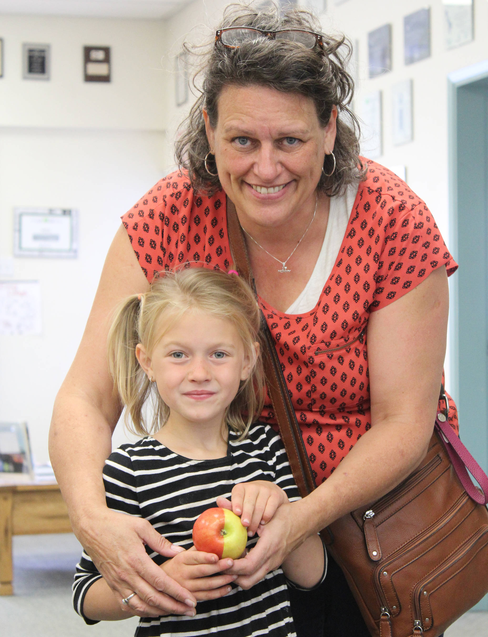 Lori Verhelst and her granddaughter Kalia Vandergaag show off the perfectly half red, half yellow apple Lori found in a bag of Pink Ladies purchased at a supermarket in Smithers. (Thom Barker photo)