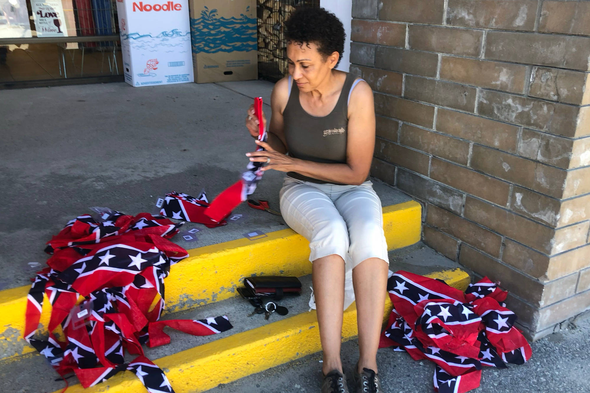 Summerland mayor Toni Boot sits in front of Your Dollar Store with More in Summerland on July 18 and destroys bandanas bearing the Confederate flag. One of the bandanas purchased at the store had been displayed for participants in an anti-racism rally on July 16. (John Arendt - Summerland Review)