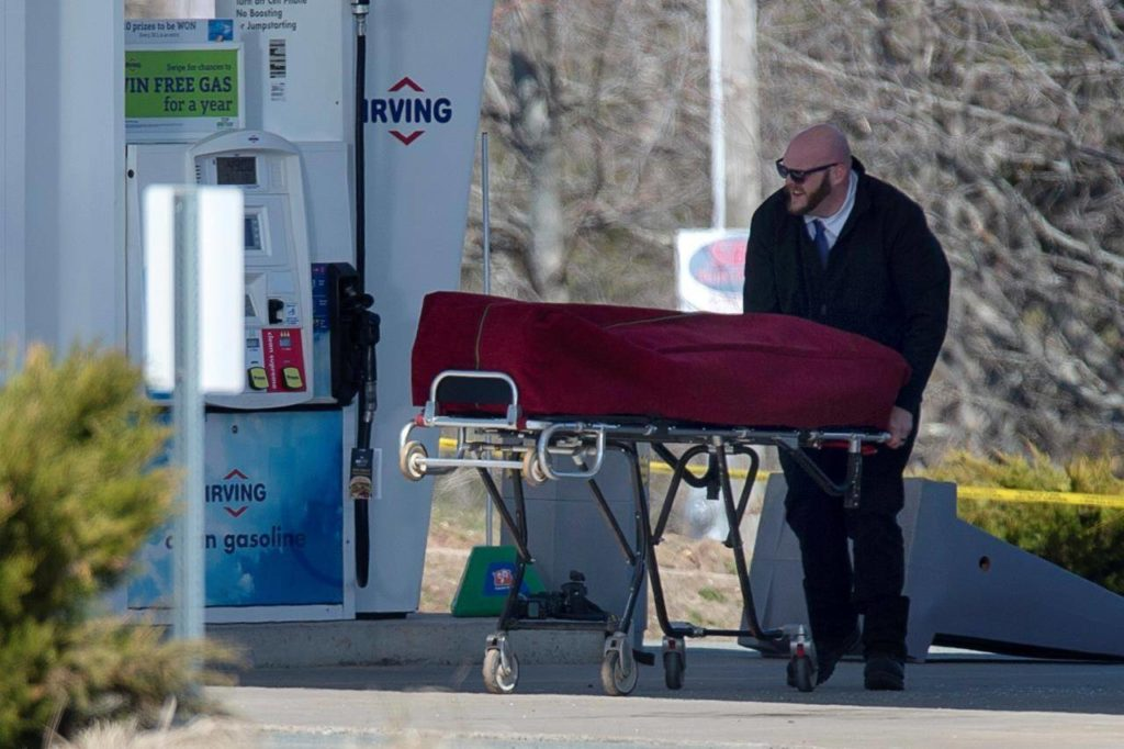 A worker with the medical examiner's office removes a body from a gas bar in Enfield, N.S. on Sunday, April 19, 2020. Over three dozen Canadian senators are calling for an inquiry into the mass shootings that left 22 people dead in Nova Scotia in April. THE CANADIAN PRESS/Andrew Vaughan