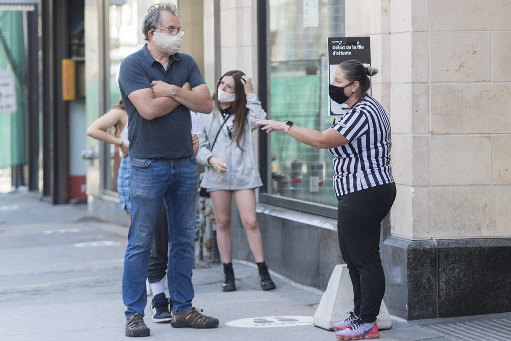 People wear face masks as they wait to enter a store in Montreal, Saturday, July 18, 2020, as the COVID-19 pandemic continues in Canada and around the world. The wearing of masks or protective face coverings is mandatory in Quebec as of today. THE CANADIAN PRESS/Graham Hughes