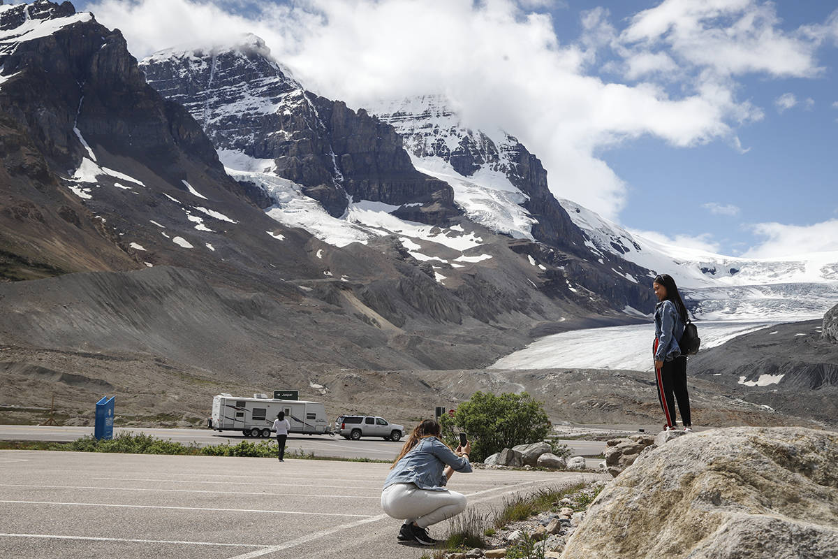 Tourists take photos at the Columbia Icefields near Jasper, Alta., Sunday, July 19, 2020. Three people were killed and more than a dozen others were critically injured when a glacier sightseeing bus rolled at one of the most popular attractions in the Rocky Mountains, the Columbia Icefield. RCMP said the rollover happened early Saturday afternoon. Pictures posted online by people at the scene showed one of the attraction's big-wheeled ice explorers on its roof down a moraine embankment. THE CANADIAN PRESS/Jeff McIntosh