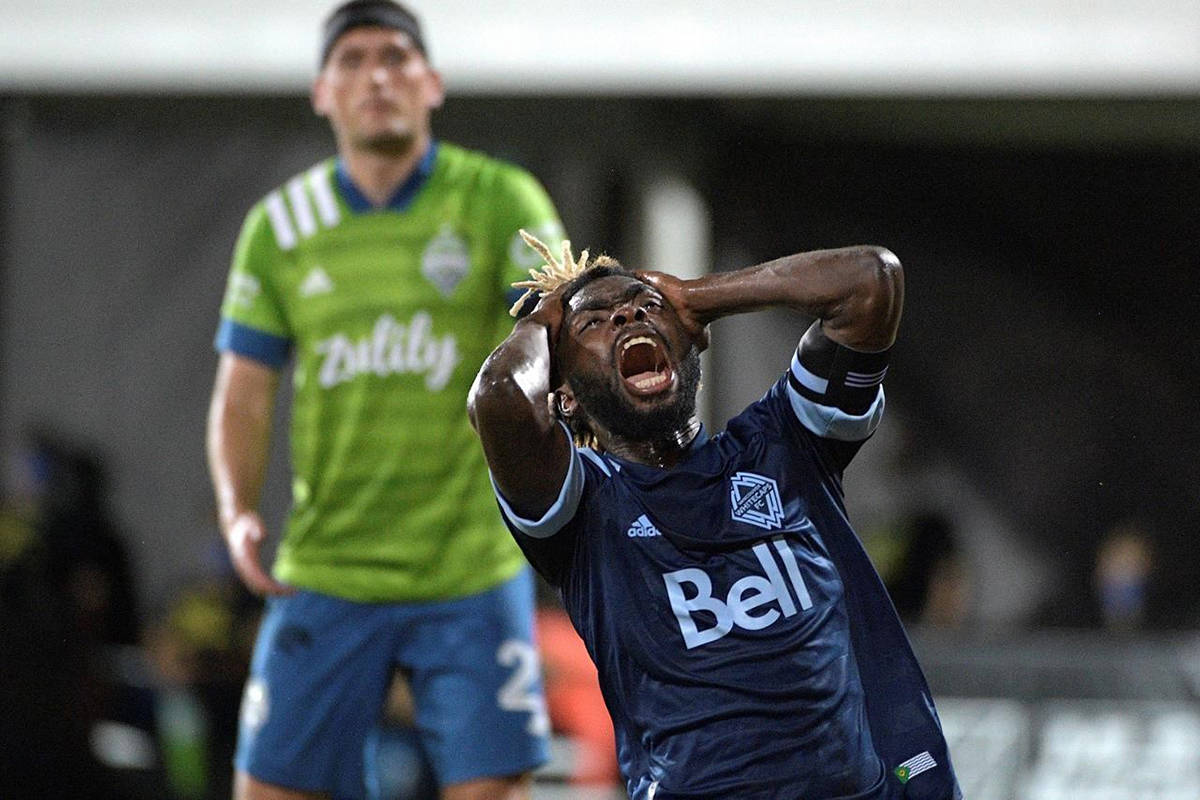 Vancouver Whitecaps midfielder Leonard Owusu reacts after missing a shot on goal as Seattle Sounders defender Shane O'Neill, left, watches during the first half of an MLS soccer match, Sunday, July 19, 2020, in Kissimmee, Fla. (AP Photo/Phelan M. Ebenhack)