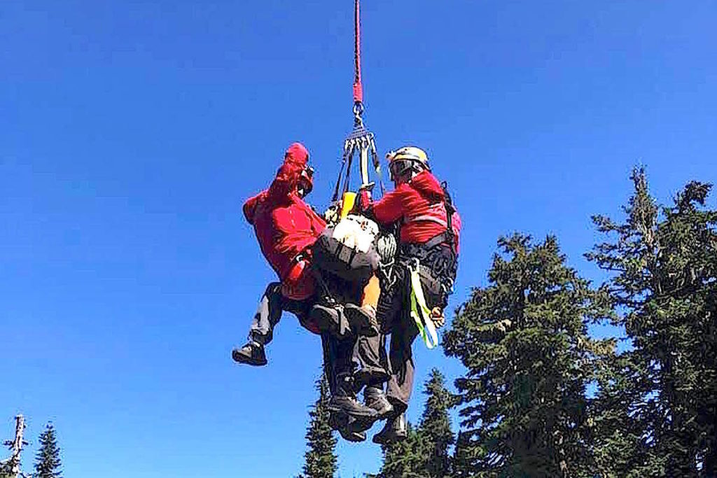 FILE – Two specially trained members of the Chilliwack SAR team arrive on solid ground with the pair of climbers from Mt. Slesse. (Chilliwack SAR/Tony)