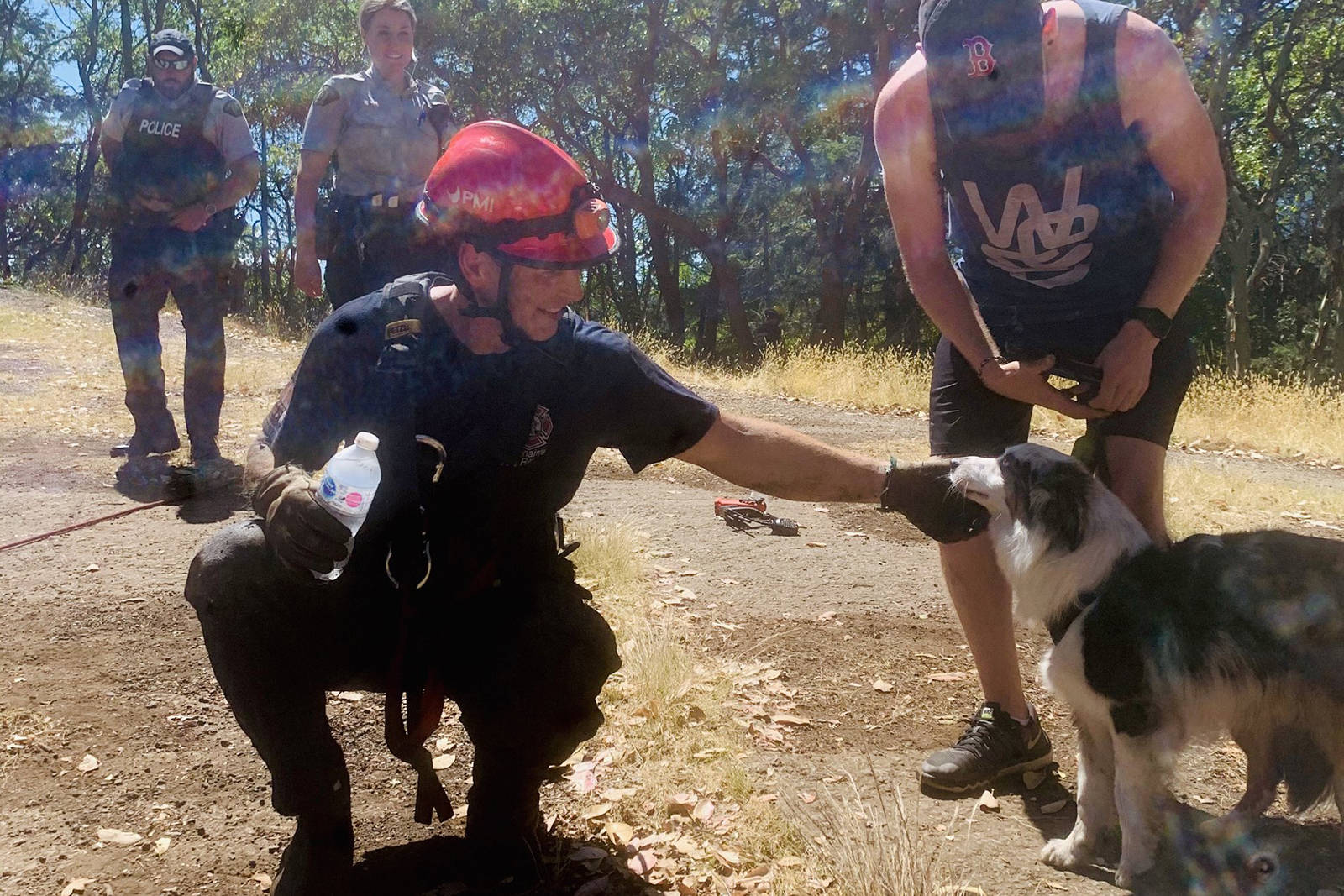 Nanaimo Fire Rescue firefighter Justin Lynch shares a moment with Joey, an Australian shepherd, after he went down into the Abyss to rescue the dog that had fallen about 18 metres into the crack in the bedrock that runs along much of the Extension Ridge near Nanaimo on Tuesday. (Nanaimo Fire Rescue photo)