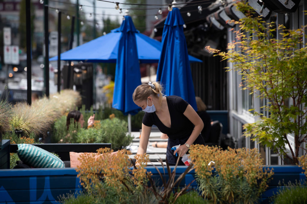 A server wears a face mask while cleaning a table on the patio at an Earls restaurant, in Vancouver, on Tuesday, May 19, 2020. THE CANADIAN PRESS/Darryl Dyck