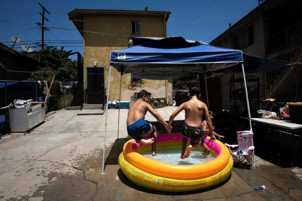 Children jump into an inflatable pool in Los Angeles, Friday, July 17, 2020. Inflatable pools are driving a deluge of toy sales during the COVID-19 pandemic as consumers look to reclaim a few gallons of summer and enhance at-home leisure for their children, their pets and their feet. THE CANADIAN PRESS/AP/Jae C. Hong