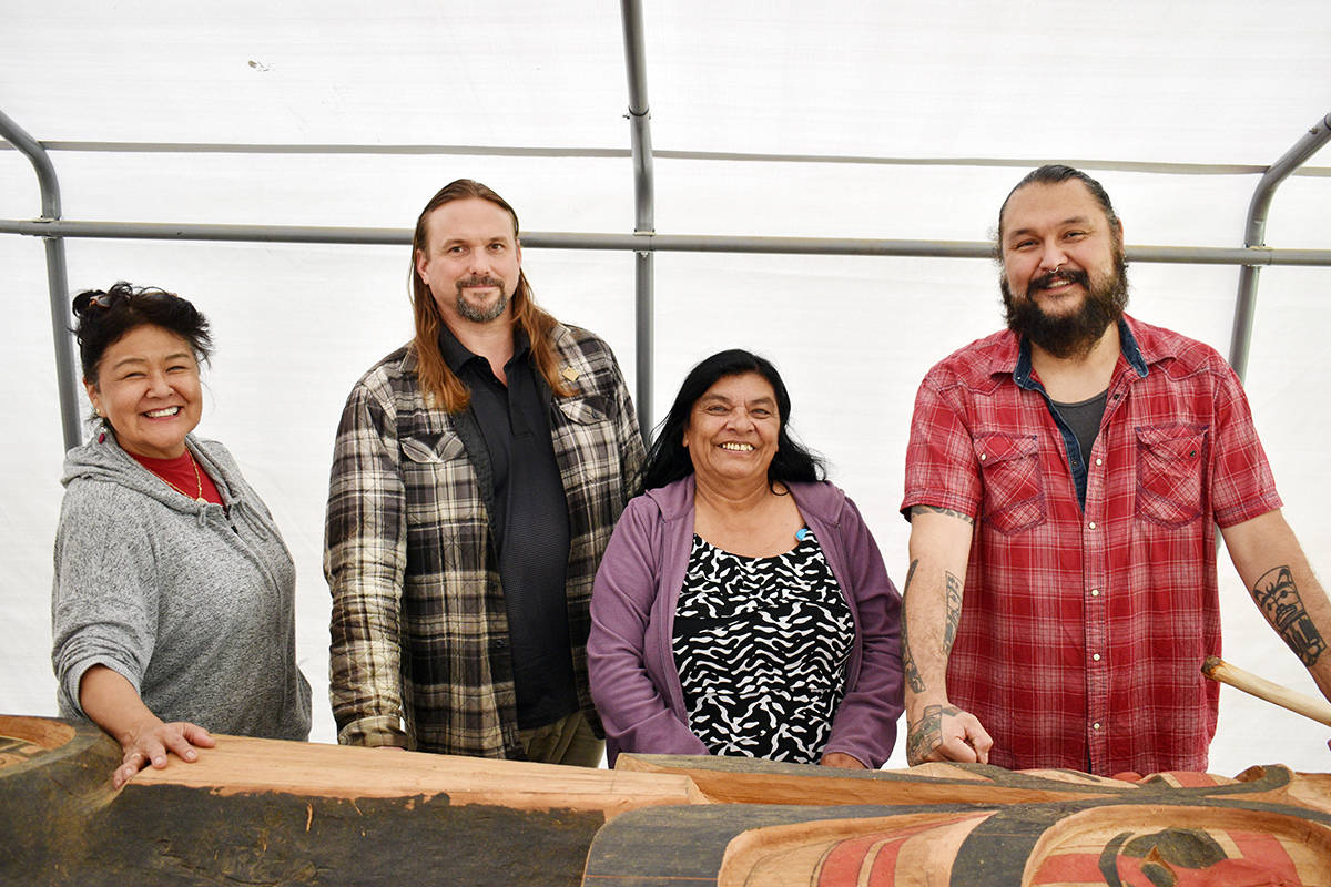 A memorial totem pole in honour of missing and murdered Indigenous women will be raised in September. Organizers Arlene Roberts, Marc Snelling and Gladys Radek along with carver Mike Dangeli are seen here with the partially-finished pole under a tent in Dangeli's back yard on Terrace's Southside July 16, 2020. (Jake Wray/Terrace Standard)