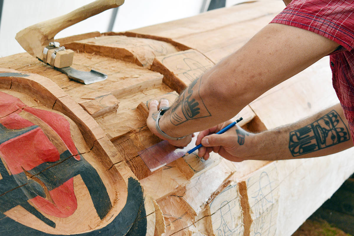 Artist Mike Dangeli sketches a figure on the Highway of Tears memorial totem pole he is carving under a tent in his back yard in Terrace on July 22. (Jake Wray/Terrace Standard)