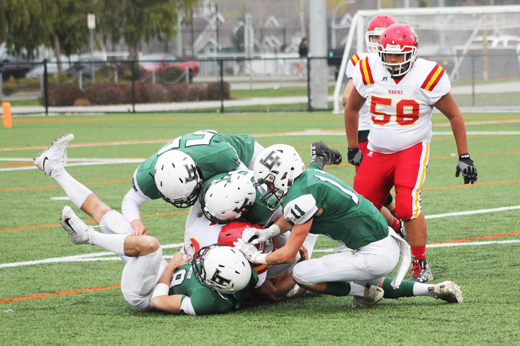 Lord Tweedsmuir football players swarm a lone W.J. Mouat Hawk Nov. 8, 2019 at Cloverdale Athletic Park. High school athletes still don't know whether they will be playing sports this fall or not. (Photo: Malin Jordan)