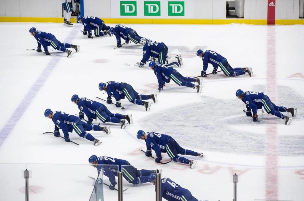 Vancouver Canucks crawl on the ice after losing a split-squad scrimmage during the NHL hockey team's training camp in Vancouver, on Wednesday, July 15, 2020. The 24 teams playing for the Stanley Cup arrived Sunday in the hub cities of Toronto and Edmonton. THE CANADIAN PRESS/Darryl Dyck