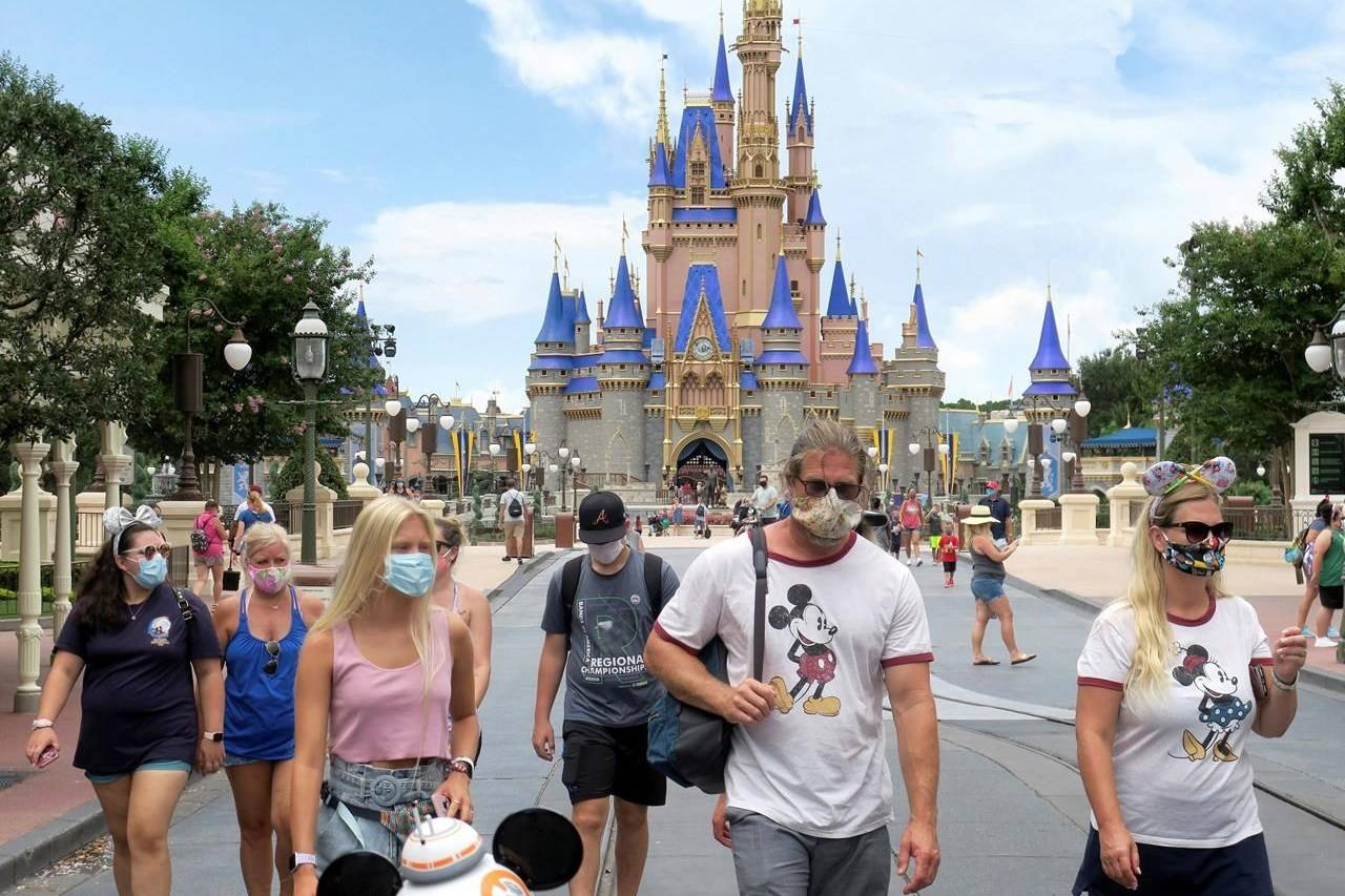 FILE - In this Saturday, July 11, 2020, file photo, guests wear masks as required to attend the official reopening day of the Magic Kingdom at Walt Disney World in Lake Buena Vista, Fla. Two weeks after reopening, workers at Disney World are praising the company for the safety protocols that have been implemented to protect against the new coronavirus. But questions remain about whether it will matter to paying guests of Disney World and its crosstown rivals, Universal Orlando and SeaWorld Orlando. (Joe Burbank/Orlando Sentinel via AP, File)