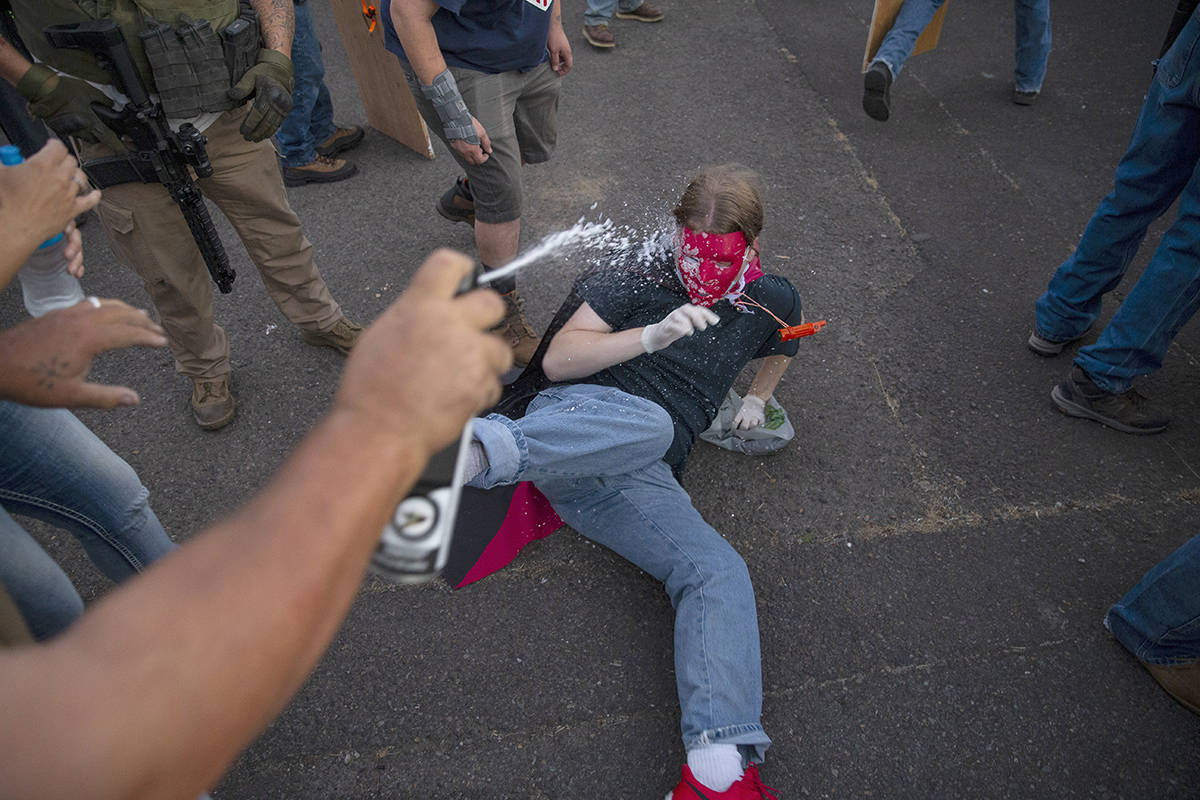 A protesters is sprayed with a chemical after being pushed to the ground during a clash in front of the Federal Courthouse in Eugene, Ore. Saturday July 26, 2020. Authorities declared a riot early Sunday in Portland, Oregon, where protesters breached a fence surrounding the city's federal courthouse where U.S. agents have been stationed. (Chris Pietsch/The Register-Guard via AP)