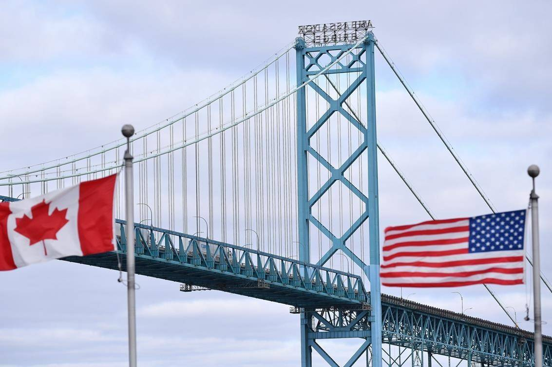 Canadian and American flags fly near the Ambassador Bridge at the Canada-USA border crossing in Windsor, Ont. on Saturday, March 21, 2020. The federal government appears to have relaxed restrictions at the Canada-U.S. border that would have made it impossible for first-year university students from the United States to enter the country. THE CANADIAN PRESS/Rob Gurdebeke