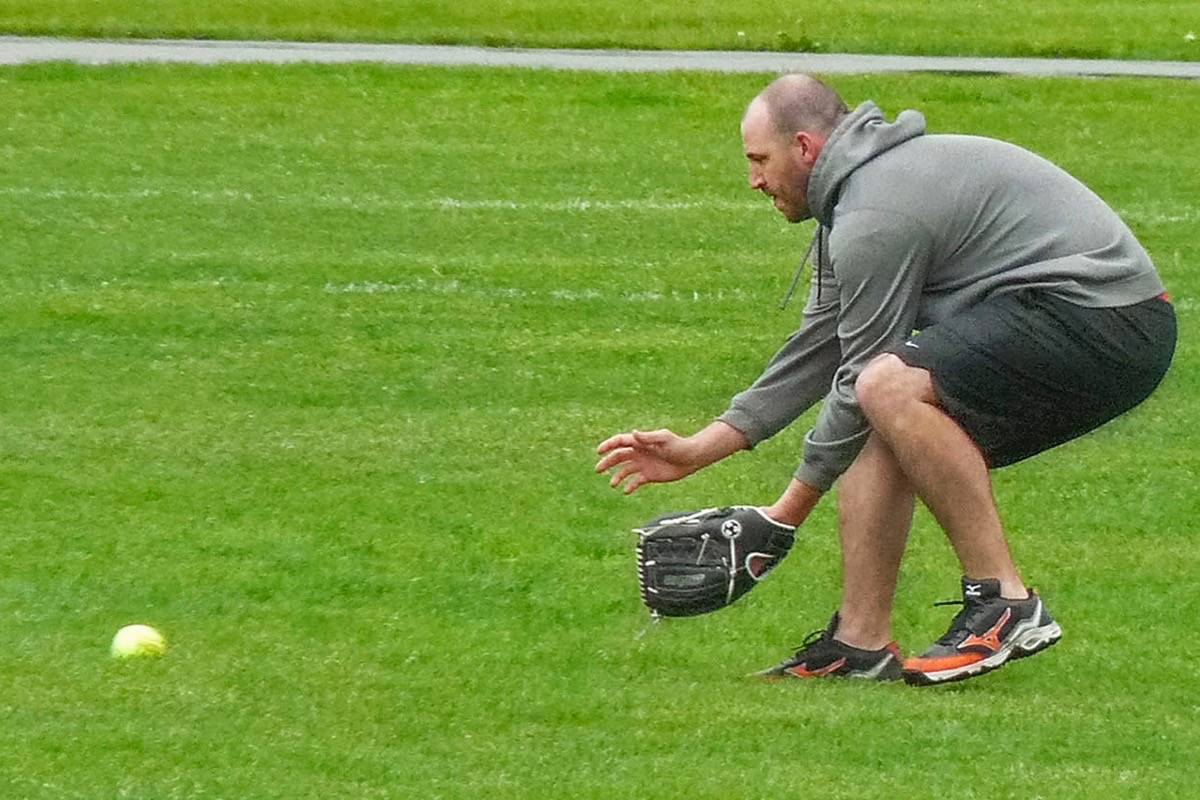 Mike Hughston of the Langley Benders, part of the Langley Mixed Slo-Pitch league, moved to intercept a rolling ground ball during a damp slo-pitch tournament at McLeod Athletic Park in May 2014 (Langley Advance Times file photo)