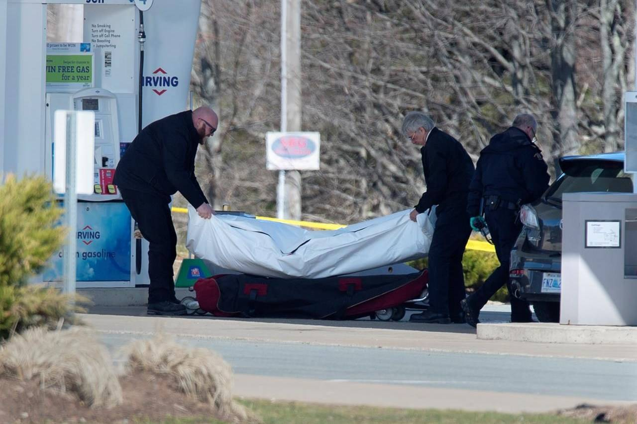 Workers with the medical examiner's office remove a body from a gas bar in Enfield, N.S. on April 19, 2020. Three Liberal MPs from Nova Scotia have come forward to challenge a decision by Ottawa and the province to conduct a joint review into the mass shootings in April that claimed 22 lives. Darren Fisher, the MP for Dartmouth-Cole Harbour, issued a statement today saying the gravity of the tragedy demands an independent public inquiry, which would have more authority than a joint review. THE CANADIAN PRESS/Andrew Vaughan