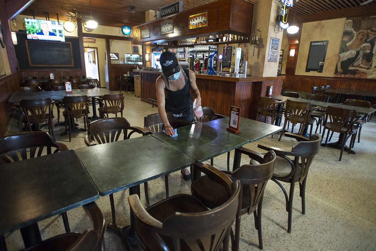 """A server cleans tables at an empty pub, Wednesday, July 22, 2020 in Montreal. A coalition of business groups is calling for """"urgent action"""" from all levels of government to save the food service industry amid the economic fallout from the COVID-19 pandemic.THE CANADIAN PRESS/Ryan Remiorz"""