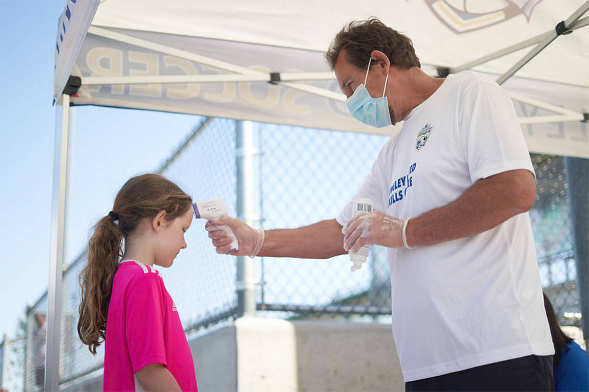 A young player gets her temperature checked by technical director Mark Parker at a Langley United Soccer Association training session at Willoughby park (Courtesy Langley United)