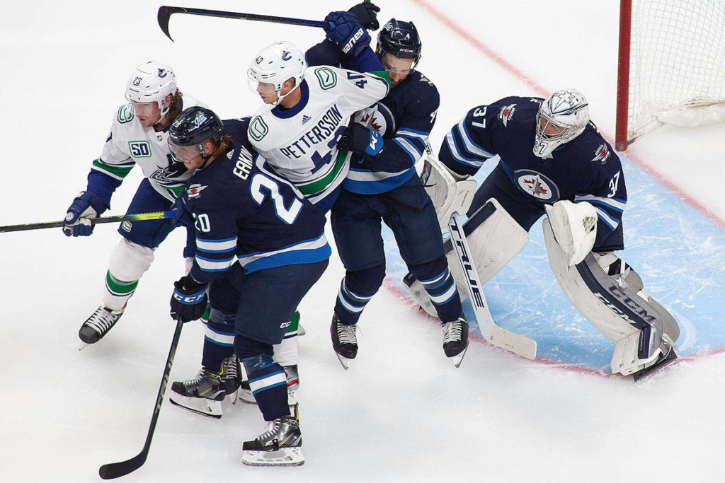 Winnipeg Jets' Neal Pionk (4) battles hard against Vancouver Canucks' Elias Pettersson (40) in front of Jets goaltender Connor Hellebuyck during second period NHL exhibition game action in Edmonton, on Wednesday, July 29, 2020. THE CANADIAN PRESS/Codie McLachlan