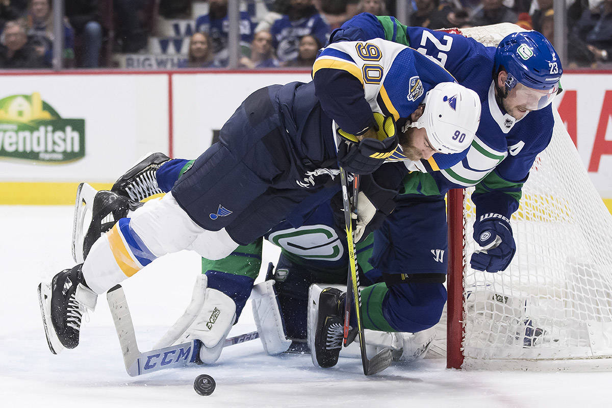 Vancouver Canucks' Alexander Edler (23), of Sweden, hauls down St. Louis Blues' Ryan O'Reilly (90) in front of goalie Jacob Markstrom, back, of Sweden, during the third period of an NHL hockey game in Vancouver, on Tuesday November 5, 2019. The Canucks meet the Minnesota Wild in 2020 'play-in' series action. THE CANADIAN PRESS/Darryl Dyck