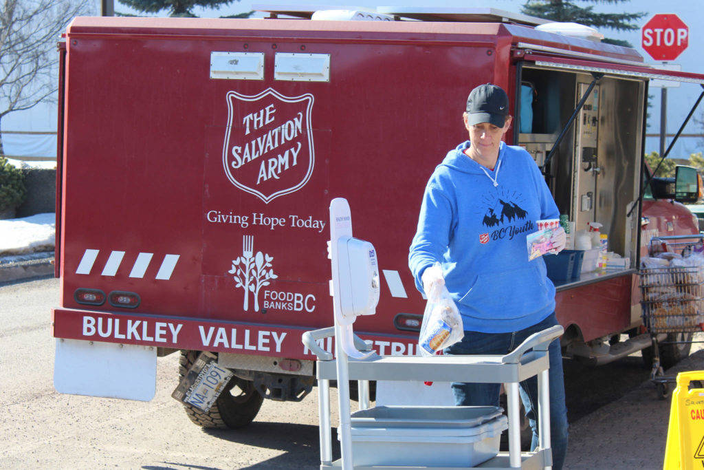 Kelly Spurway hands out bag lunches on Main Street in Smithers out of the Salvation Army's mobile community service unit. (Thom Barker photo)