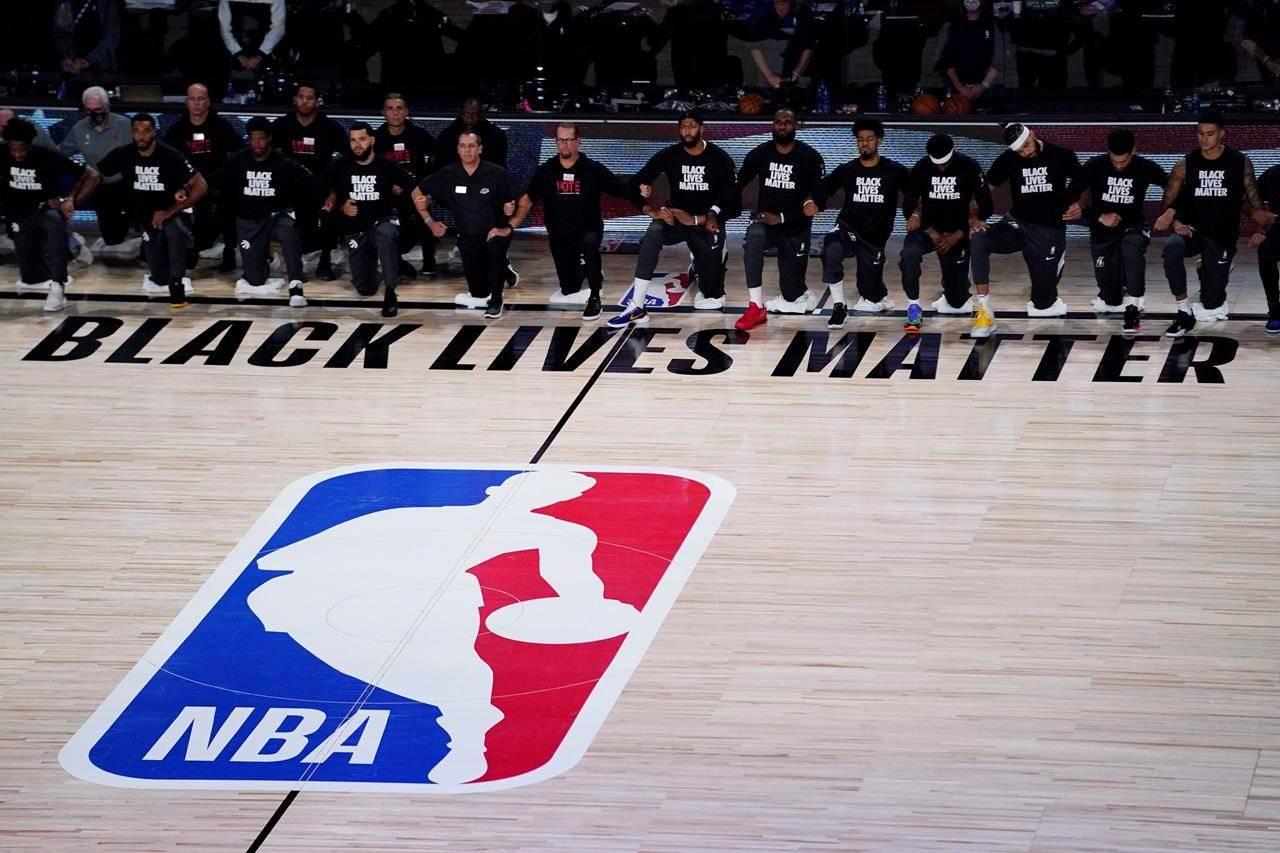 Players kneel before an NBA basketball game between the Los Angeles Lakers and the Toronto Raptors, Saturday, Aug. 1, 2020, in Lake Buena Vista, Fla. (AP Photo/Ashley Landis, Pool)