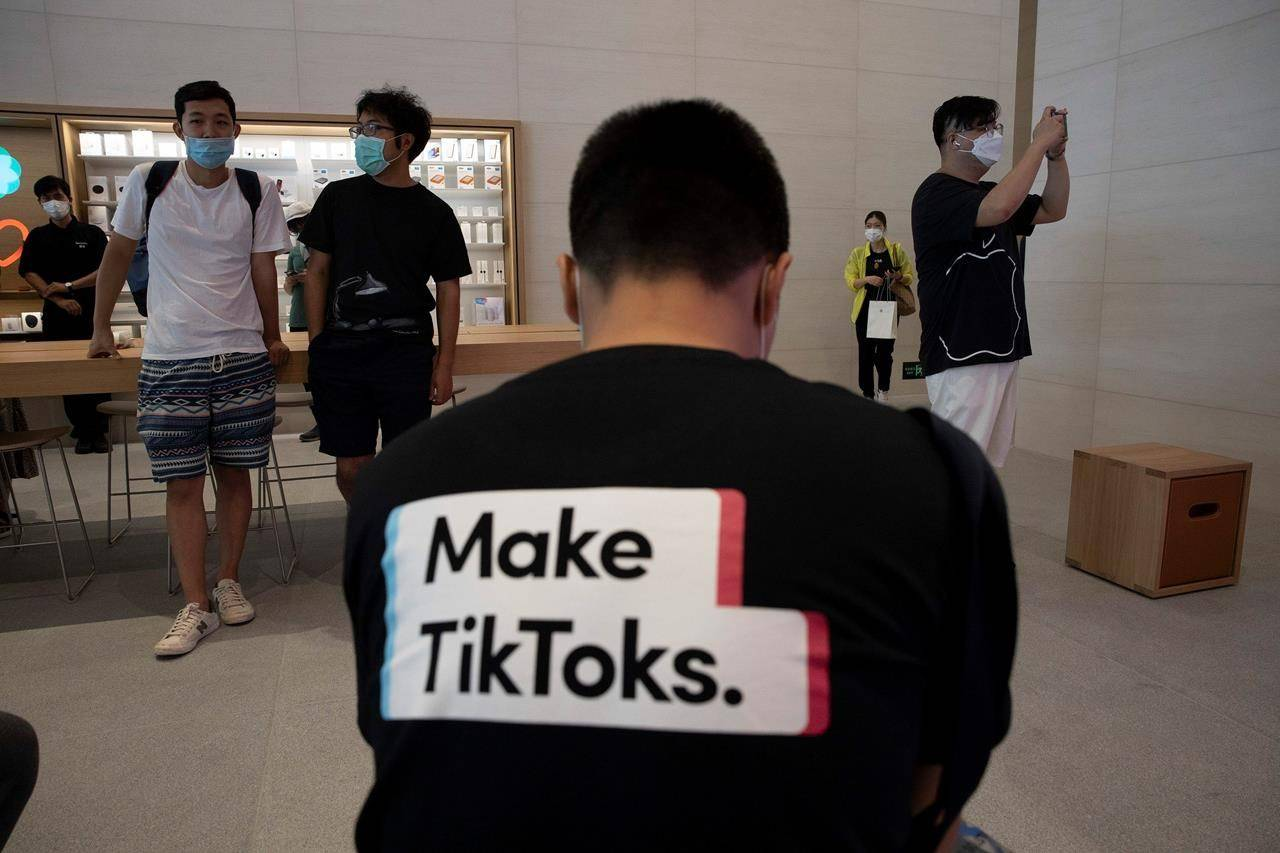 A man wearing a shirt promoting TikTok is seen at an Apple store in Beijing on Friday, July 17, 2020. U. S. President Donald Trump says he wants to take action to ban TikTok, a popular Chinese-owned video app that has been a source of national security and censorship concerns. (AP Photo/Ng Han Guan)
