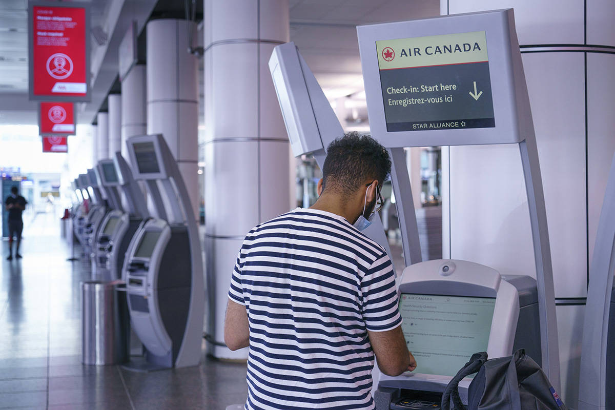 A passenger uses an Air Canada self service check-in kiosk at Montreal-Trudeau International Airport in Montreal, on Friday, July 31, 2020. THE CANADIAN PRESS/Paul Chiasson