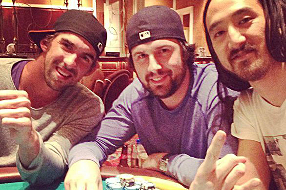Brad Booth (center) sitting at a poker table with musician Steve Aoki (right) and Olympic swimmer Michael phelps. Facebook photo.