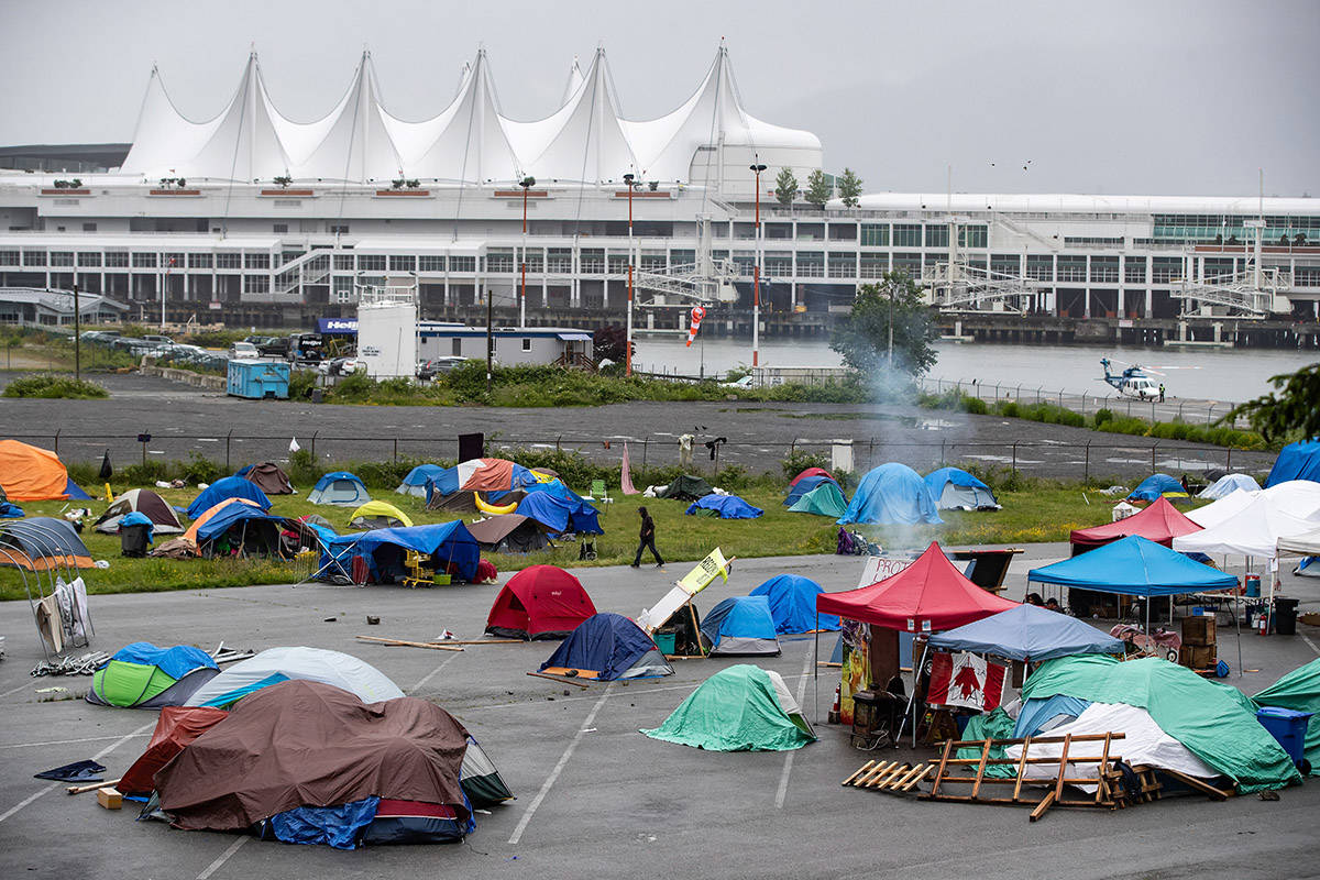 A man walks through a homeless camp where approximately 150 people are living at a parking lot on Port of Vancouver property adjacent to Crab Park, in Vancouver on June 10, 2020. THE CANADIAN PRESS/Darryl Dyck