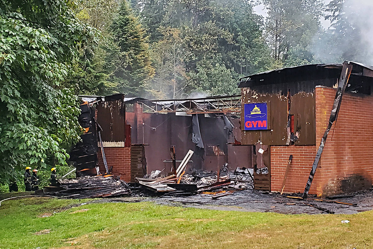 Firefighters can be seen in the lower-left side of the photo hosing down the still smouldering building at Khalsa Centre summer camp. The building, partially used as a gym and partially used as a storage facility, is one of 17 buildings at the camp. Photo courtesy of Sundeep Kaur.